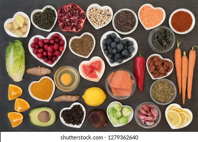 Super food to slow the ageing process concept including fish, fruit, vegetables, nuts, green & black tea, herbs, spices and dairy. High in antioxidants, anthocyanins, dietary fibre & vitamins.