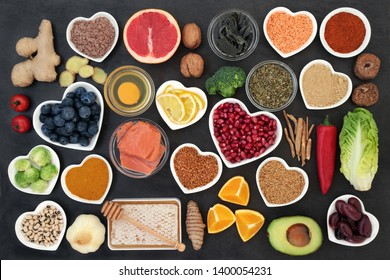 Super food to slow the ageing process concept including fish, fruit, vegetables, herbs, spices, supplement powders honey & dairy on slate. High in antioxidants, anthocyanins, dietary fibre & vitamins.