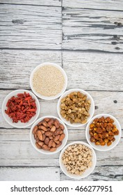 Super food tiger nuts, mulberry berries, cacao beans, goji berries, quinoa seeds, golden berry in white bowls over wooden background