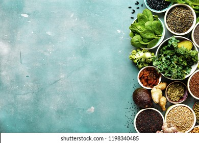 Super food or vegetarian food concept. Seeds, cereals, beans, vegetables, herbs for healthy cooking on blue stone background top view with copy space