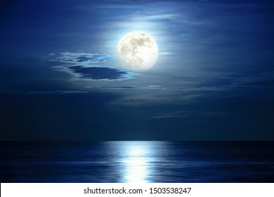 Super full moon and cloud in the blue sky above the ocean horizon at midnight, moonlight reflect the water surface and wave, Beautiful nature landscape view at night scene of the sea for background