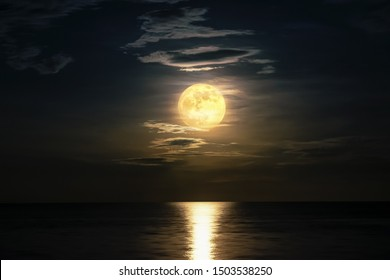 Super full moon cloudy in dark sky on the ocean horizon at midnight, Moonlight yellow gold reflects the wave water surface, Beautiful fantasy nature landscape view the sea at night scene background