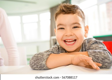 Super fun. Close up shot of a cute little boy laughing hilariously sitting at a table copyspace happiness joy laughter childhood carefree children people kids positivity expressive emotions concept