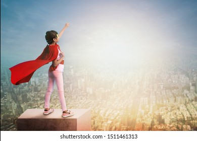 Super girl child show power on rooftop of building ,little kid wearing red hero cloak show hand up to sky and city in sun set, active dream and motivation idea concept