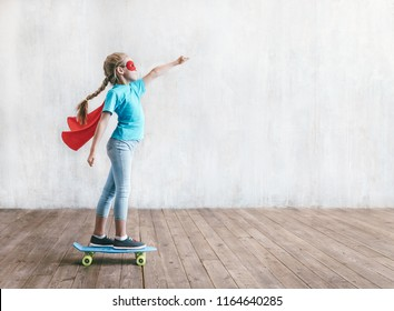 Super girl skating on a skateboard in studio