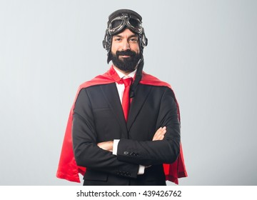 Super hero businessman with his arms crossed over grey background