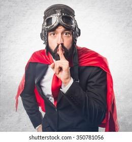 Super hero businessman making silence gesture