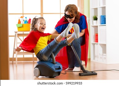 Super hero kid flying on vacuum cleaner. Mother and child daughter cleaning the room and have a fun pastime together