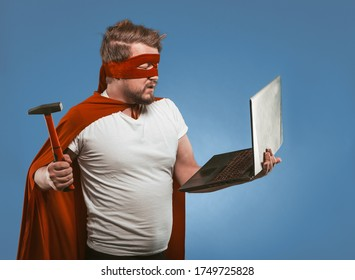 Super hero man going to smash or repair laptop computer with hammer. Side view of masked man in red super hero uniform posing on denim blue background. Computer hacking concept.