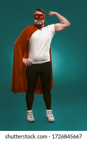 Super Hero Man Shows His Muscles And Ready To Save World. Serious Man In Red Super Hero Mask And Coat Showing His Muscles Looking At Camera. Cut Out On Biscay Green Background.