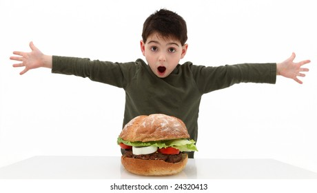 Super huge giant burger and a hungry boy.