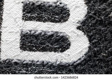 Super macro 5x closeup detail of grey fabric texture background with white print letter B on it.