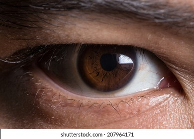 super macro shot of asian male's eye. Texture of the dark eye is visible