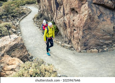 Super mom with baby boy travelling in backpack. Hiking adventure with child on autumn family trip in mountains. Vacations journey with infant carried on back, weekend travel in Tenerife, Spain.