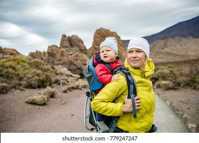 Super mom with baby boy travelling in backpack. Mother on hiking adventure with child, family trip in mountains. Vacations journey with infant carried on back, weekend travel in Tenerife, Spain.