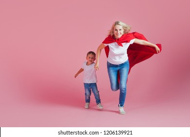 super mom and her son run forward. Fun family, a young blond woman in a red Cape as superhero, pink background