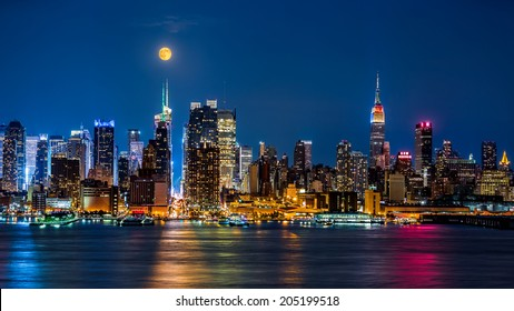 Super Moon above New York skyline. The top of the Empire State Building is illuminated with the colors of the German and Argentinian flags in honor of the Soccer World Cup final.
