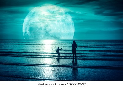 Super moon. Colorful sky with bright full moon over seascape. Silhouette of mother with her child playing in the sea. Outdoor at gloaming. The moon taken with my camera.