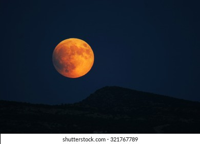 Super moon rising over hills prior to full eclipse