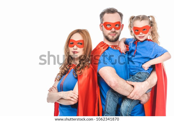 super parents with little daughter wearing masks and cloaks and looking at camera isolated on white