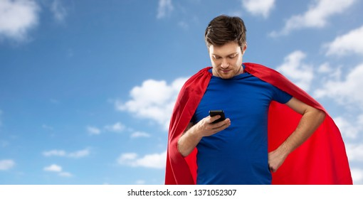 super power, technology and people concept - young man in red superhero cape using smartphone over blue sky and clouds background