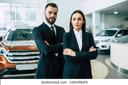 Super salesteam in dealership, two consultants or managers in black full suit with crossed arms looking on camera with smile