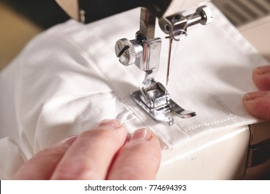 Super slow motion of a professional sewing machine stitching with white thread an Italian haute couture fabric, The seamstress sews a high fashion outfit. concept of industry, tradition, fashion