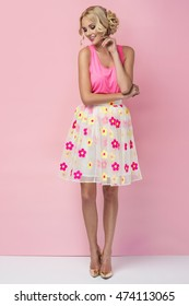 Super sweet photo of a beautiful young woman in pretty skirt with flowers and pink top. Summer fashion photo