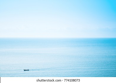 Super wide ocean view with small fishing boat and clear sky from aerial angle in Thailand