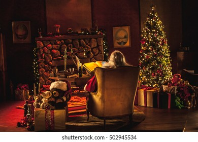 A super wide shot of Santa Claus in his workshop at the north pole, santa's office. We can see his is also using a cell phone / smart phone