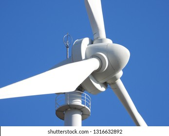 Super zoom closeup view of the big majestic white wind turbine head, tower, nacelle and three rotor blades. Renewable energy windmill standing on the field in Germany