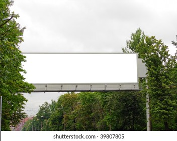 The superbig billboard among trees over the main street