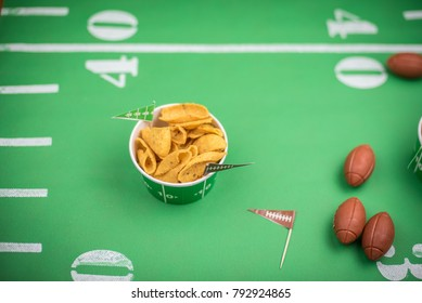 superbowl party snacks closeup on green field background