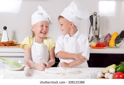 Supercilious little boy chef standing proudly with folded arms looking down on a cute little girl also in chefs uniform