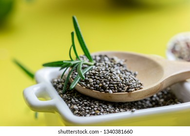 Superfood for better health concept : raw Chia seeds with rosemary leafs containing on wooden spoon