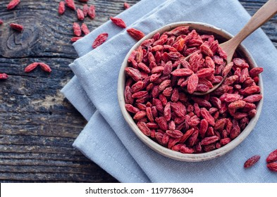 Superfood goji berries in ceramic bowl on wooden background. Wolfberry for healthy eating. Healthy super food supplement. Alternative medicine. Recovery. Rejuvenation. Slimming. Top view. Copy space.