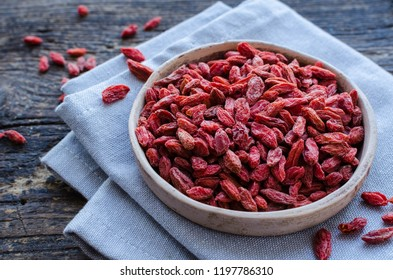 Superfood goji berries in ceramic bowl on wooden background. Wolfberry for healthy clean eating. Healthy super food supplement. Alternative medicine. Recovery. Rejuvenation. Slimming.