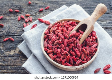 Superfood goji berries in ceramic bowl on wooden background. Wolfberry for healthy eating. Healthy super food supplement. Alternative medicine. Recovery. Rejuvenation. Slimming.
