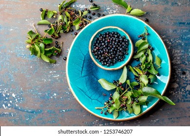 Superfood MAQUI BERRY. Superfoods antioxidant of indian mapuche, Chile. Bowl of fresh maqui berry and maqui berry tree branch on metal background, top view