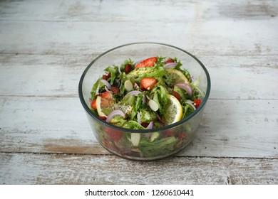 Superfood Salad Bowl. Avocado slices, Lettuce, Strawberry slices with chia seeds lemon honey dressing.