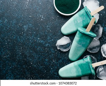Superfood spirulina popsicles on dark blue background.Ideas and recipes for healthy breakfast,summer vegetarian snack,vegan dessert. Popsicle with spirulina powder and coconut milk.Top view.Copy space