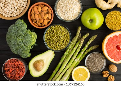 Superfood or vegetarian food concept.Vegetables,fruits,legumes,nuts and bee pollen on the black wooden background.Top view.