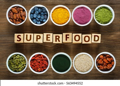 Superfoods as acai powder, turmeric, matcha green tea, spirulina, quinoa, pumpkin seeds, blueberry, dried goji berries, cape gooseberries (physalis peruviana), raw cocoa, hemp seeds on wooden table