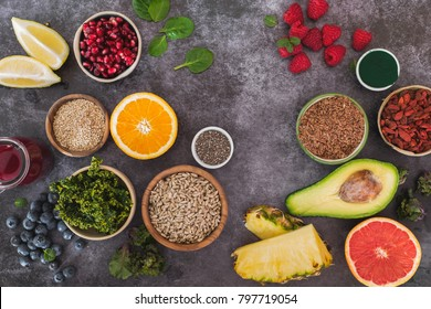 Superfoods. An arrangement of superfoods featuring seeds, legumes, fruits and vegetable. Top view, blank space, dark background