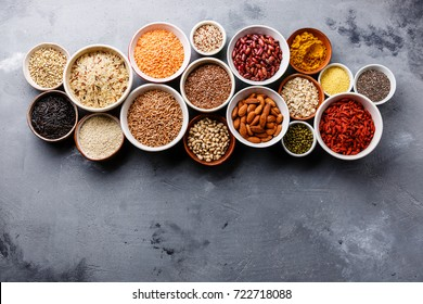 Superfoods and cereals selection in bowls: quinoa, chia, goji berry, mung bean, buckwheat, bean, turmeric, polba, bulgur, lentil, sesame, flax seed, wild rice, almond on concrete background copy space
