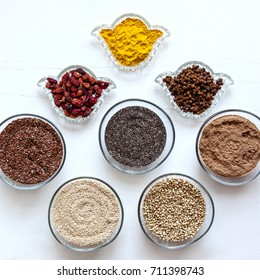Superfoods in glassware on white background. Bright colorful flat lay of healthy food products.