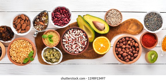 Superfoods Healthy food. Nuts, berries, fruits, and legumes. On a white wooden background. Top view. Free copy space.