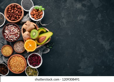 Superfoods Healthy food. Nuts, berries, fruits, and legumes. On a black stone background. Top view. Free copy space.