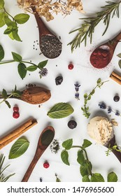 Superfoods: maca powder, beetroot powder, chia and hemp, spirulina in wooden spoons on a white background. Healthy eating concept.