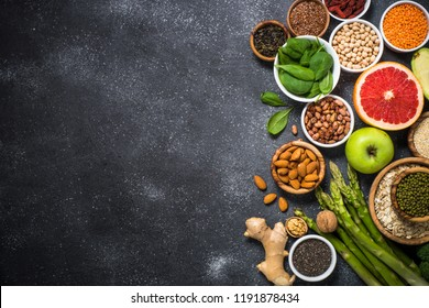 Superfoods on black stone background. Legumes, nuts, chia, avocado, grapefruit, beans, goji, green apple and asparagus and quinoa. Top view copy space.